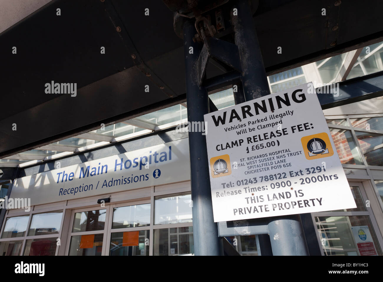 Warning sign illegal parking clamping release fee outside Hospital Reception - Stock Image