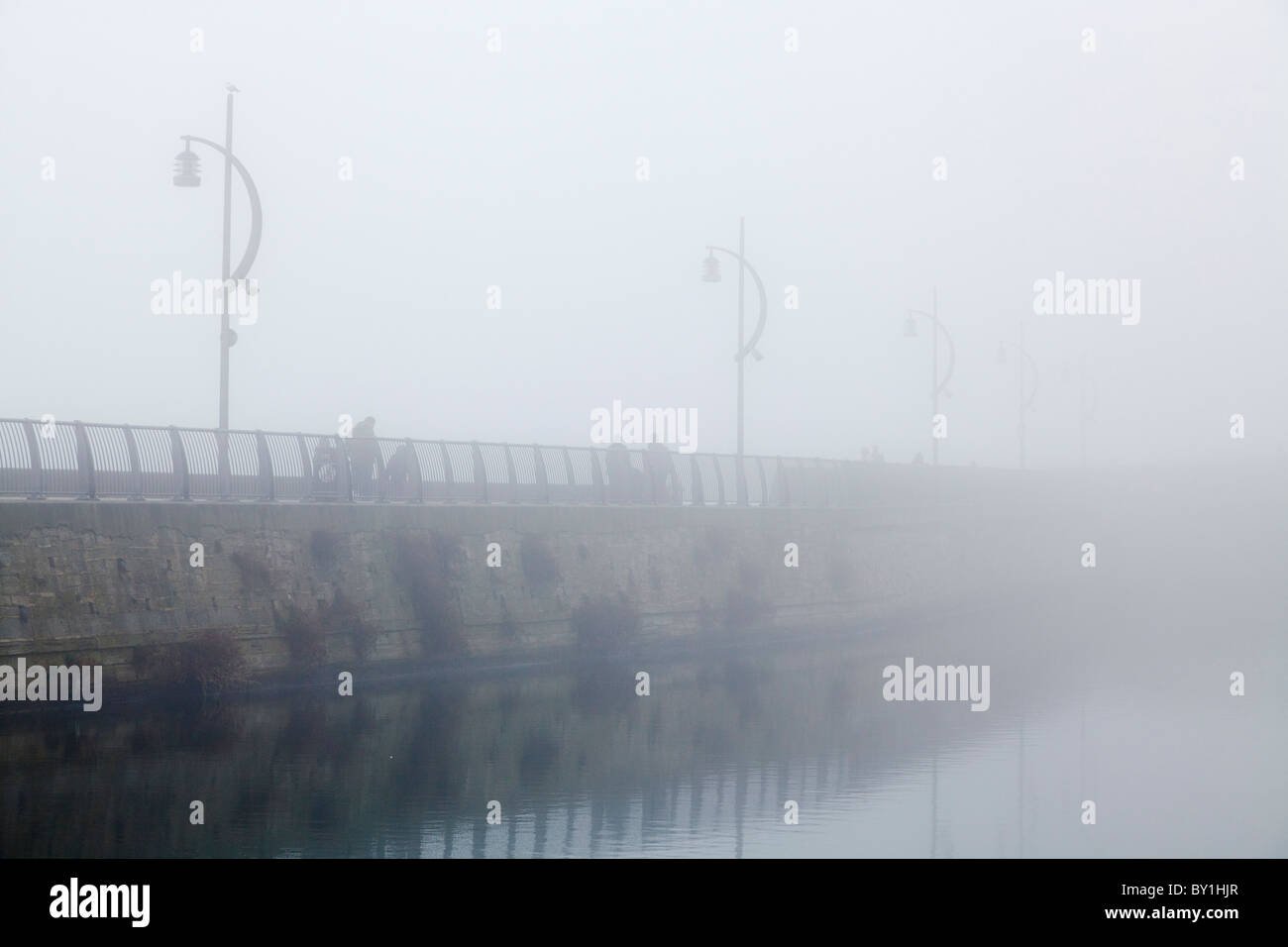 people walking on sea wall on a foggy day with unlit street lamps - Stock Image