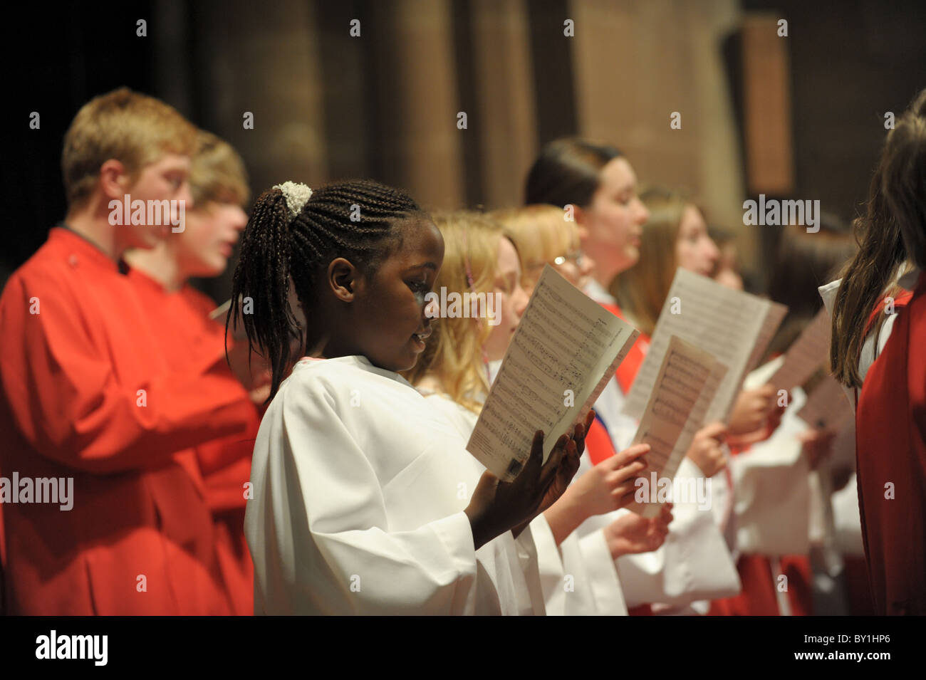 Church choir with black and white children in cassocks holding sheet music practising for a choral concert - Stock Image