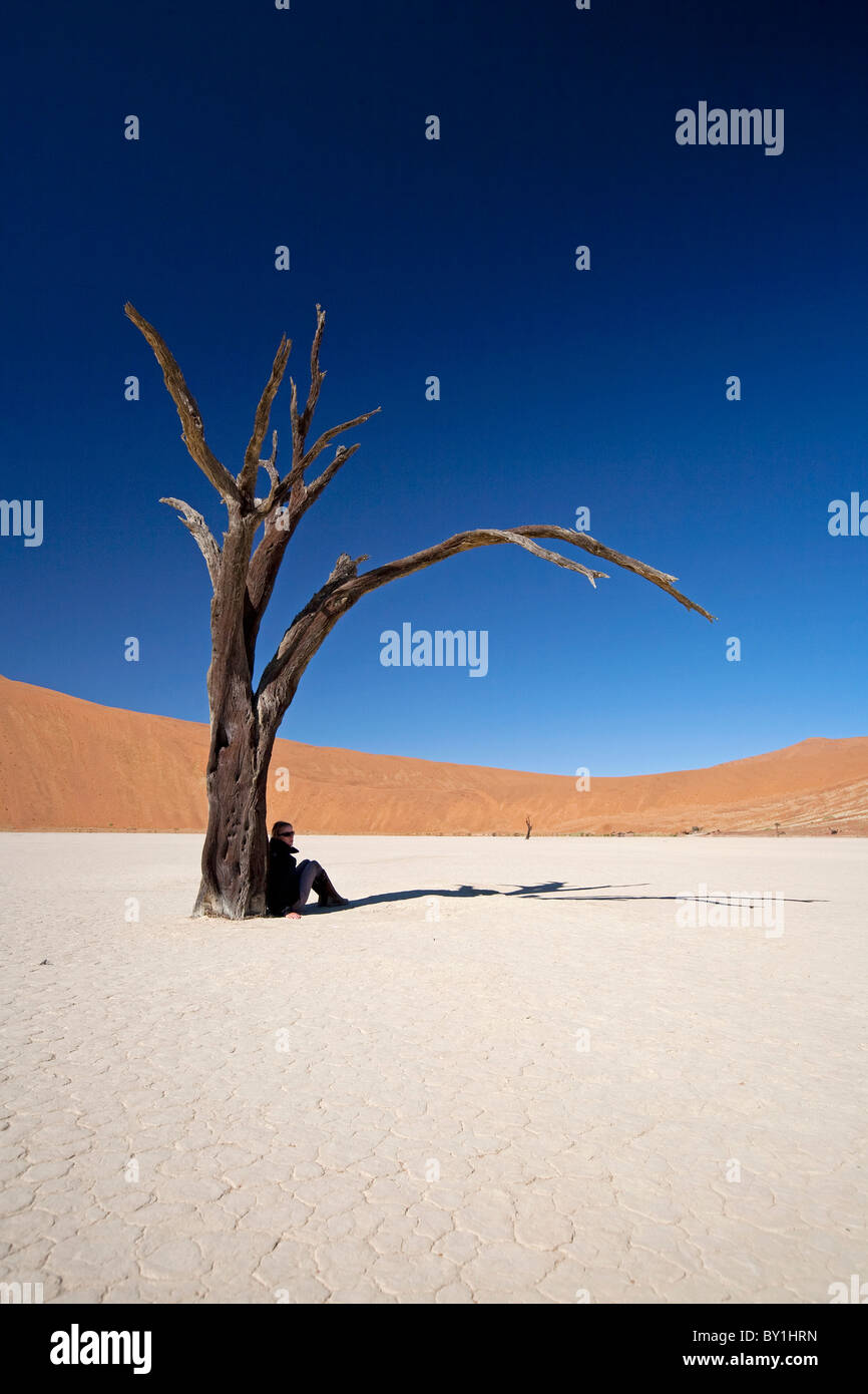 Namibia, Deadvlei. A tourist finds a spec of shade under one of the ancient dead trees of Deadvlei. - Stock Image