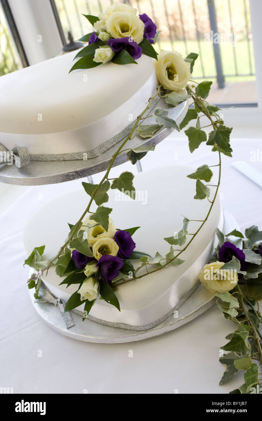Two tier white wedding cake draped in purple and cream flowers with ivy - Stock Image