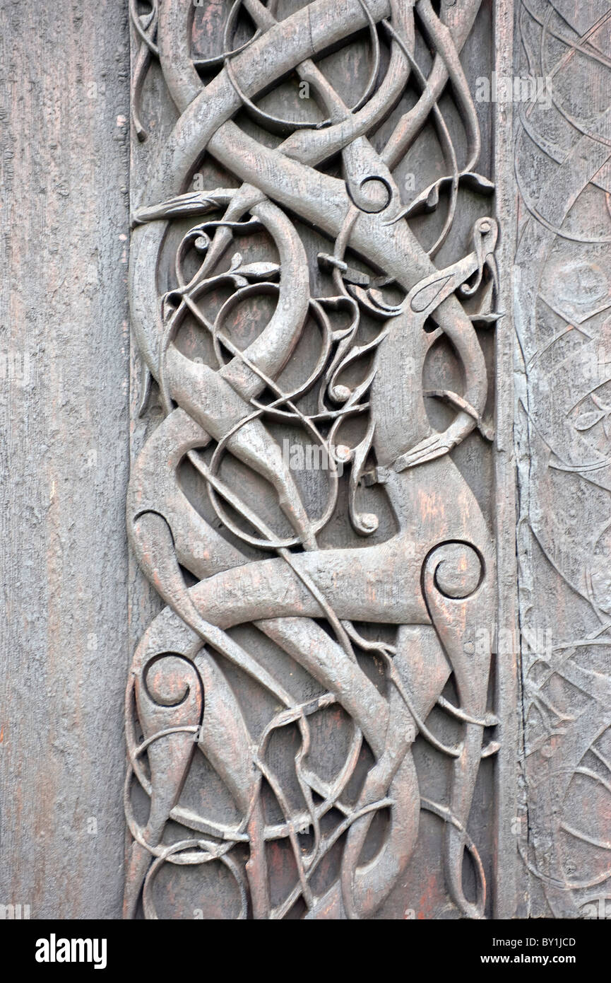 Norway, Urnes, Stave Church. A door panel on the outside wall, depicting mythical creatures entwined among foliage. - Stock Image