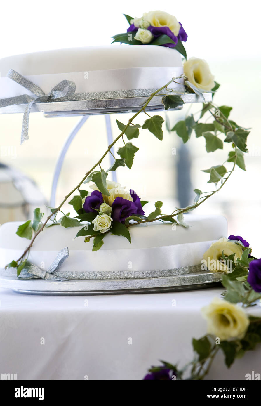 Two tier white wedding cake draped in purple and cream flowers with ...
