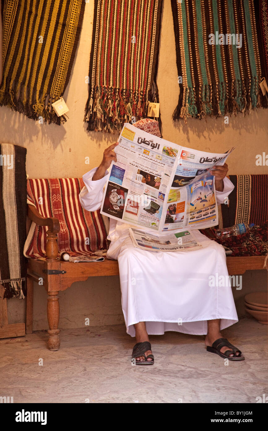Oman, Nizwa. A shop keeper passes the time with a newspaper. - Stock Image