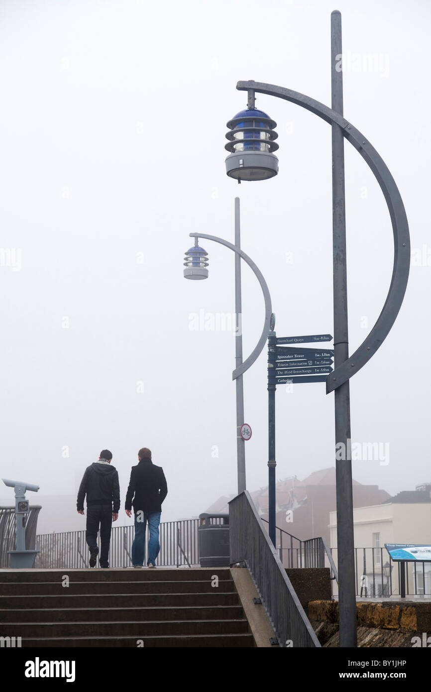 walking on sea wall in fog with street lamps - Stock Image