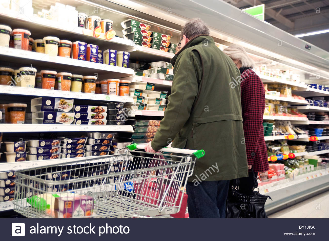 Couple shopping in an Asda supermarket, UK. Man & woman with a shopping trolley inside the store. - Stock Image