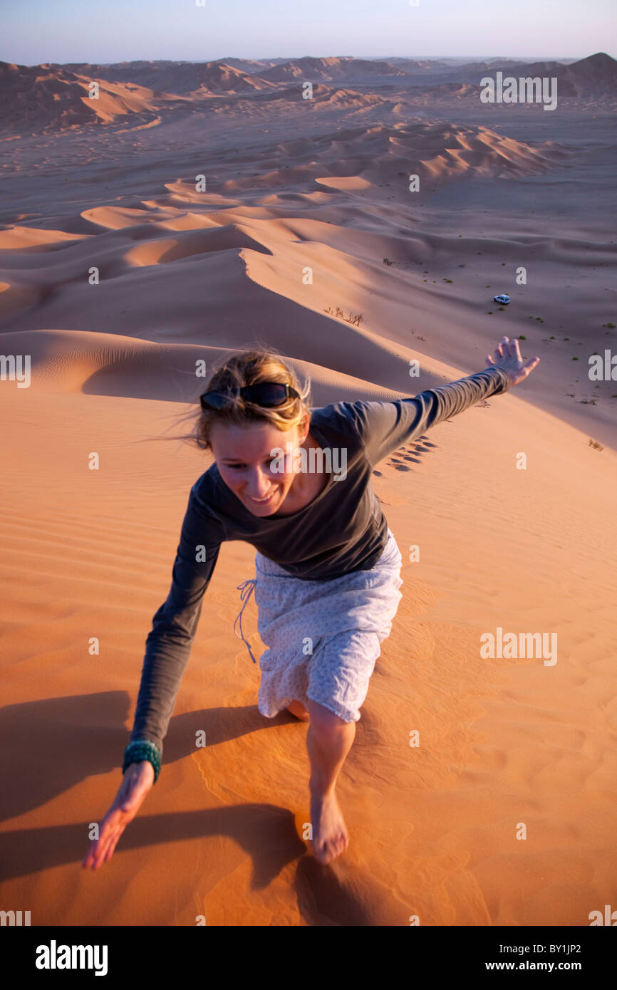 Oman, Empty Quarter. A young lady makes her way up the steep dunes. MR. - Stock Image