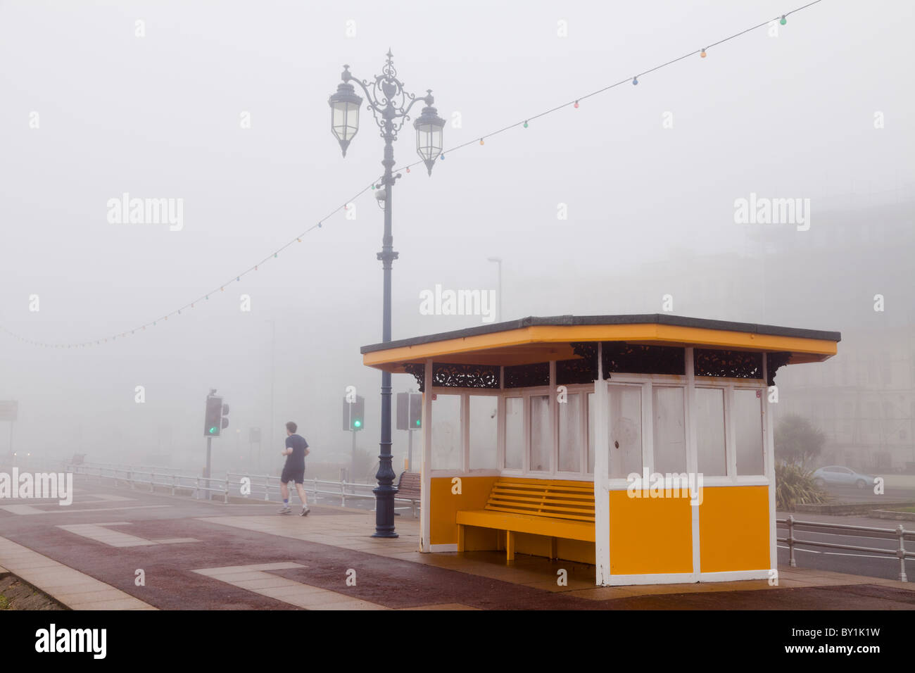 jogging in the fog on the seafront promenade in winter past a shelter - Stock Image