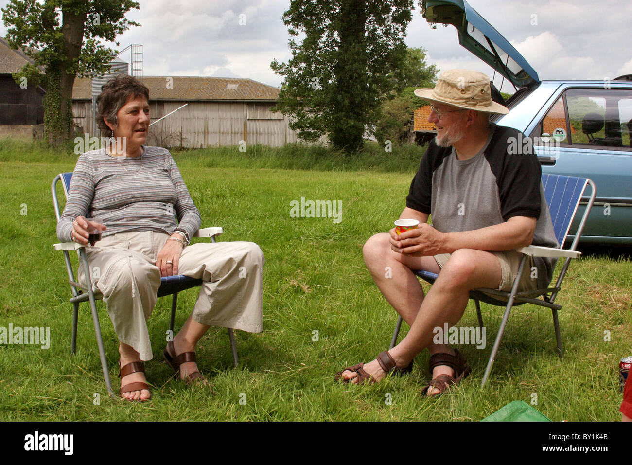 Typical English scene with old couple eating a picnic in the countryside by the parked car - Stock Image