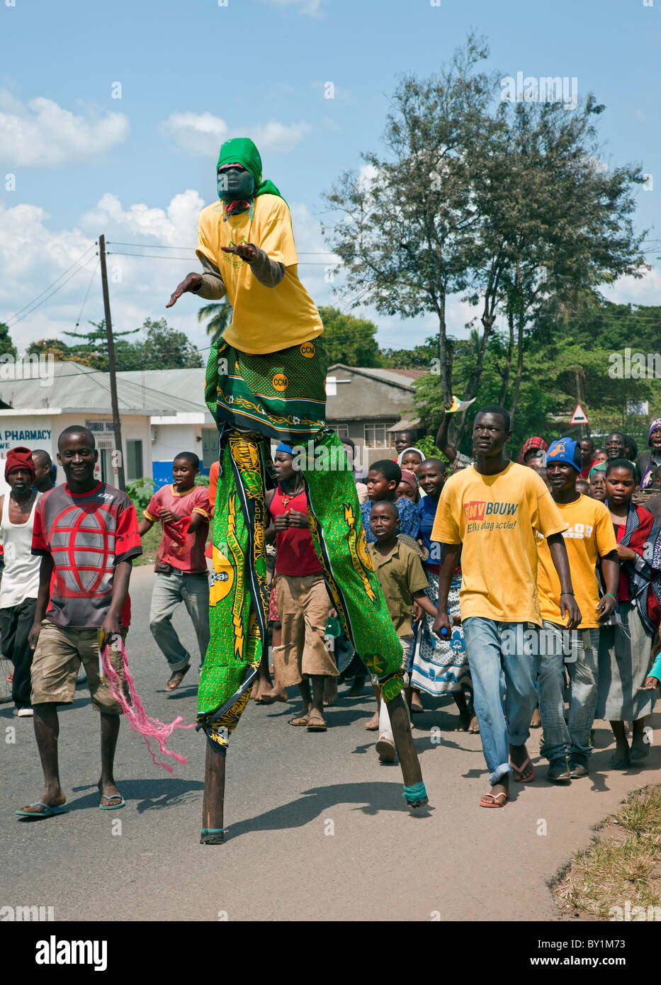 A stilt-walker leads a group of youths and children through the streets of Kerogwe prior to a political rally. - Stock Image