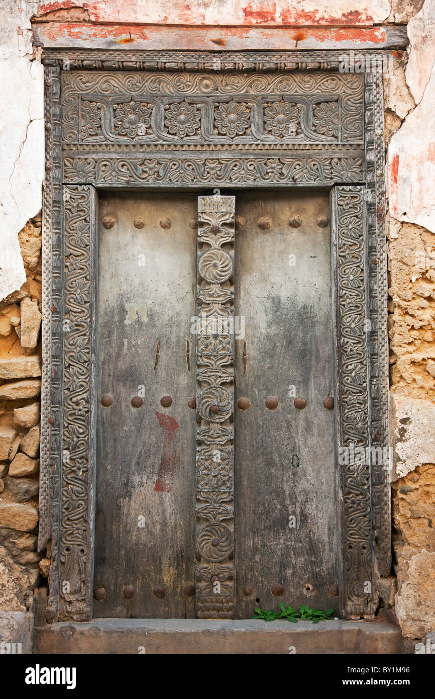 The beautifully carved wooden door frame of a derelict house in Bagamoyo  s main street. When the German colonialists - Stock Image