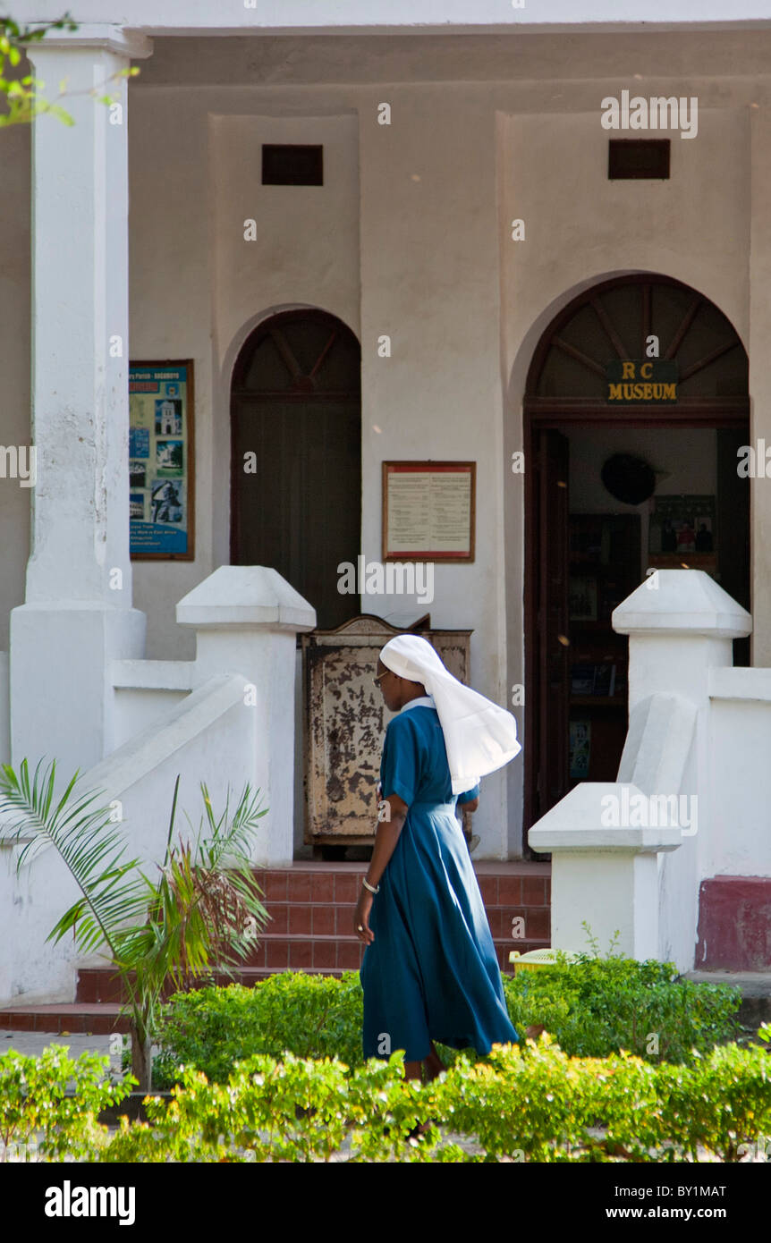 A nun walks past the entrance to the interesting Catholic Museum at the Holy Ghost Catholic Mission in Bagamoyo. - Stock Image