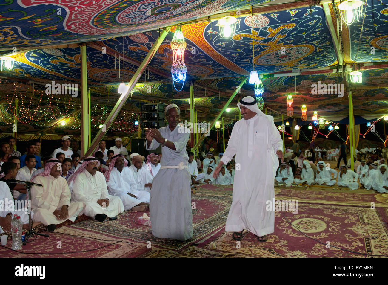 Guests celebrate with dance as other guests look on during a traditional Bedouin wedding celebration. El Tur, Sinai, - Stock Image