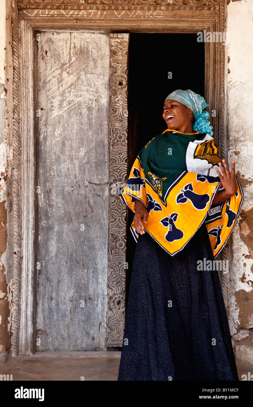 A jovial woman at the traditional carved wooden doorway to her house at Kaole, north of Dar-es-Salaam. - Stock Image