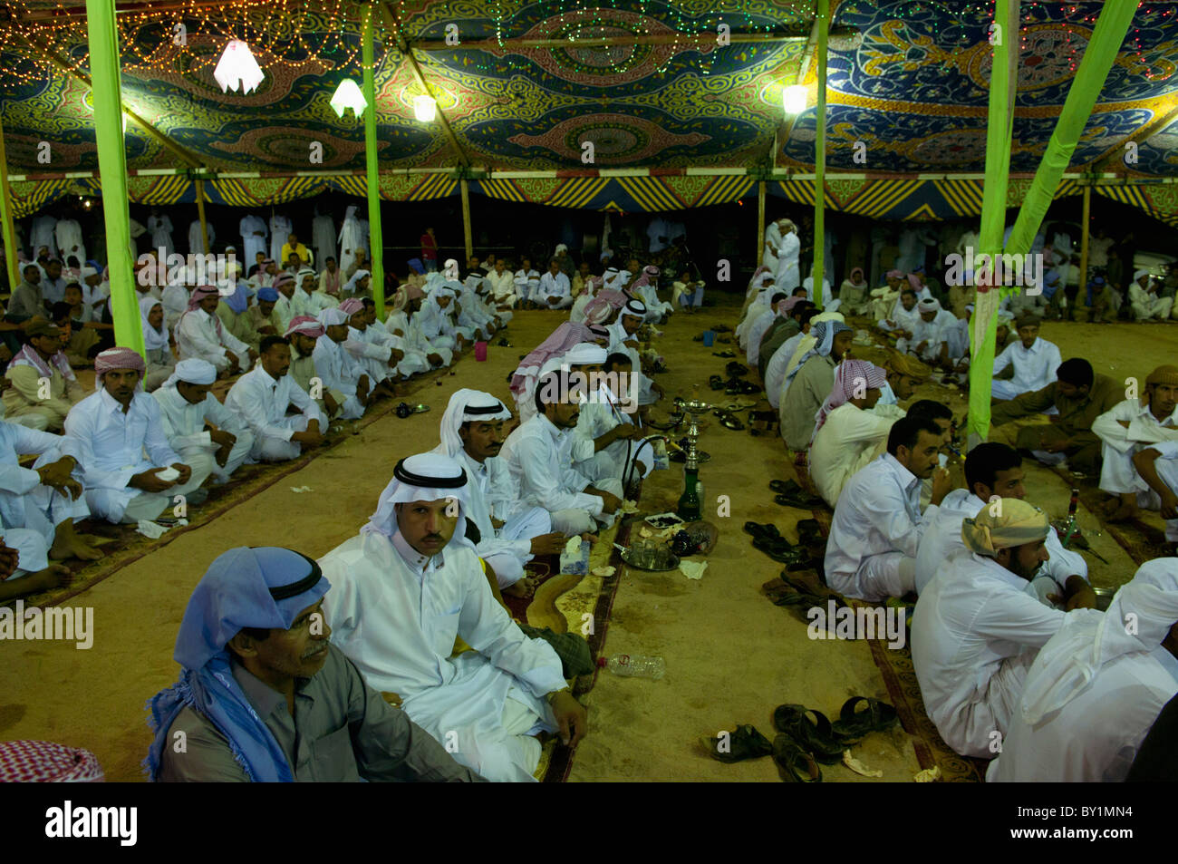 Seated guests await entertainment during a traditional Bedouin wedding celebration. El Tur, Sinai Peninsula, Egypt - Stock Image