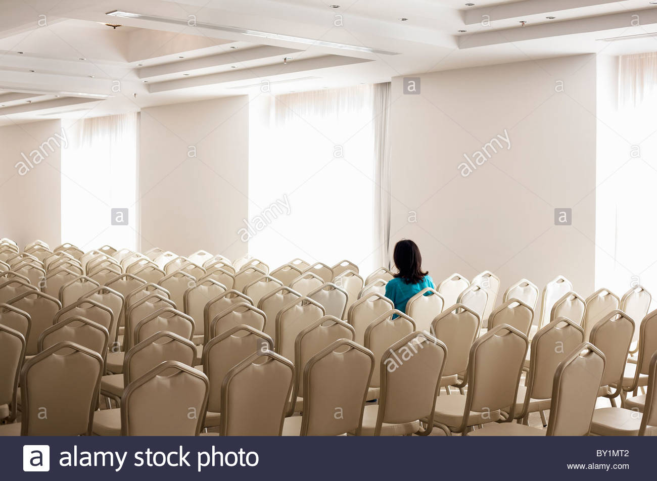 Solitary woman amongst empty chairs - Stock Image