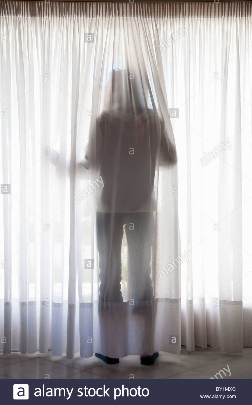 Silhouette of figure through curtains - Stock Image