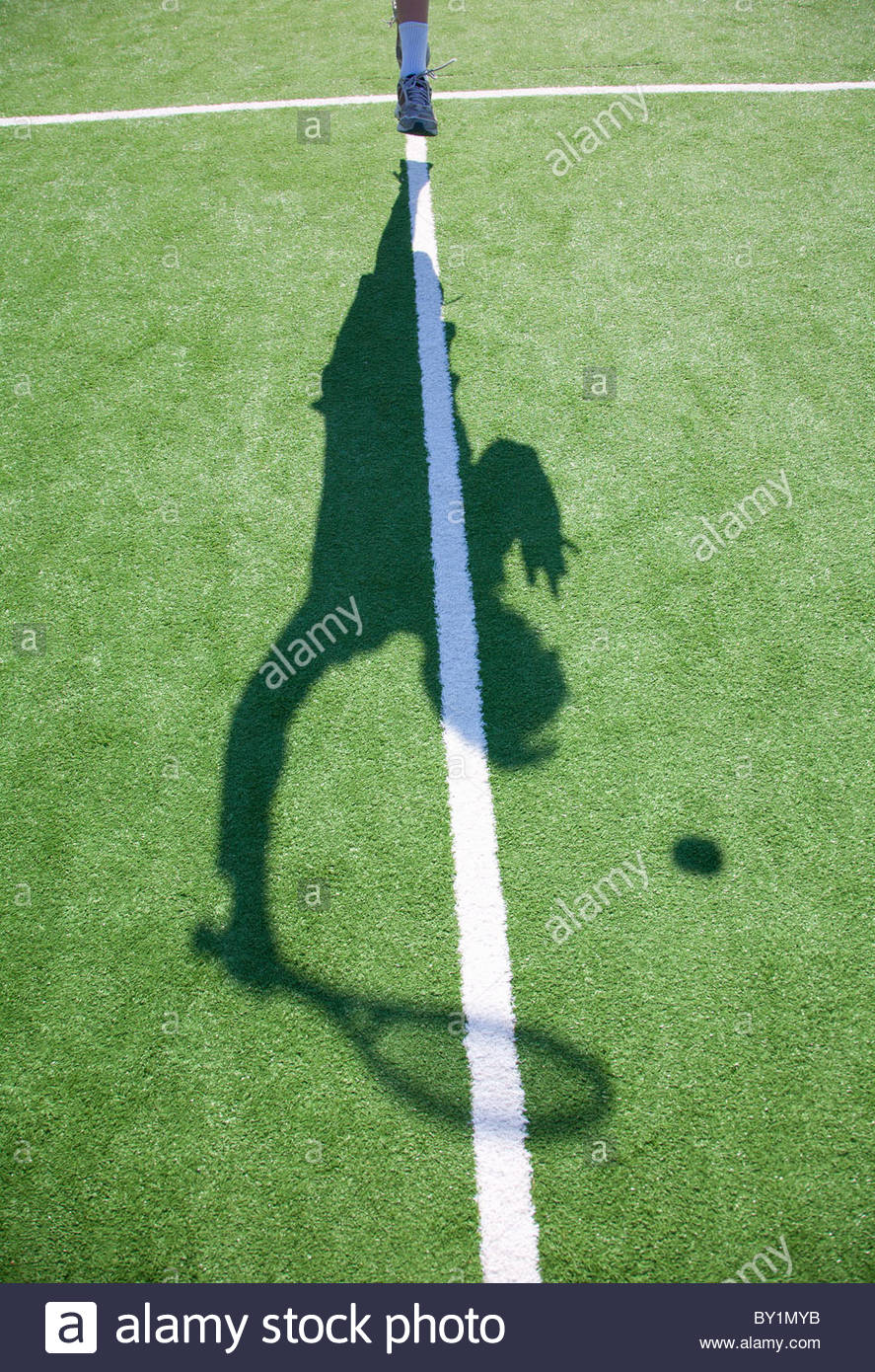 Shadow of figure serving tennis ball - Stock Image