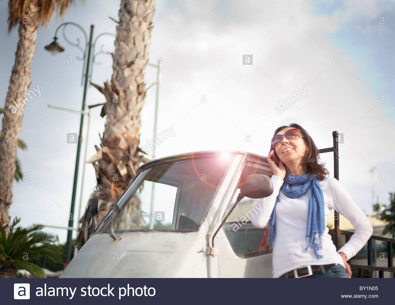 Woman on phone by small van Stock Photo
