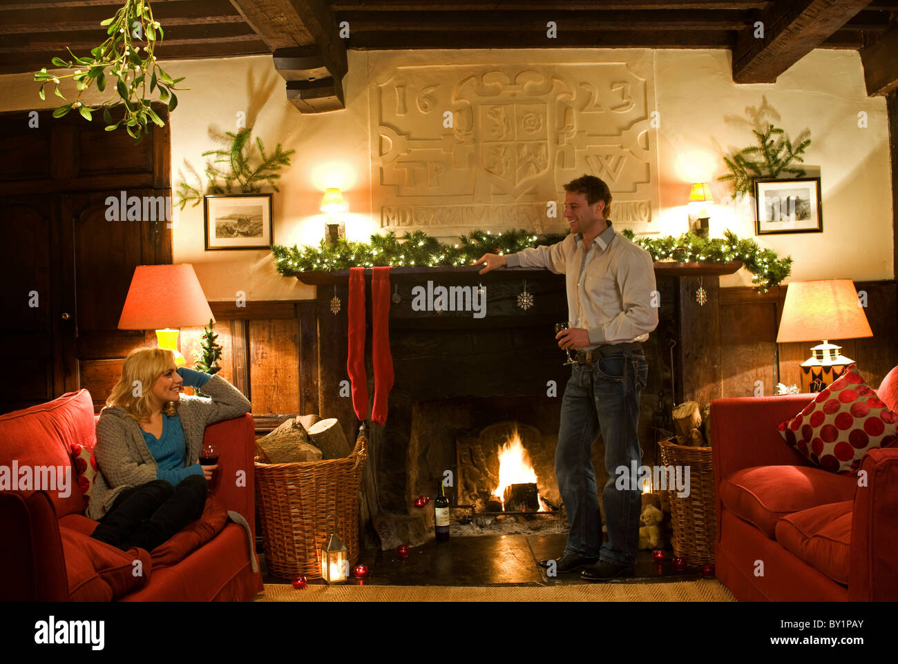 Gilar Farm, Snowdonia, North Wales.  A couple relax in the sitting room at Gilar at Christmas. - Stock Image