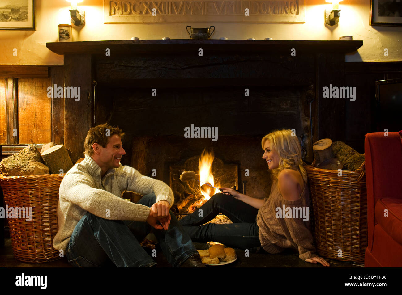 Gilar Farm, Snowdonia, North Wales.  A couple relax while toasting crumpets on the open fire in the sitting room - Stock Image