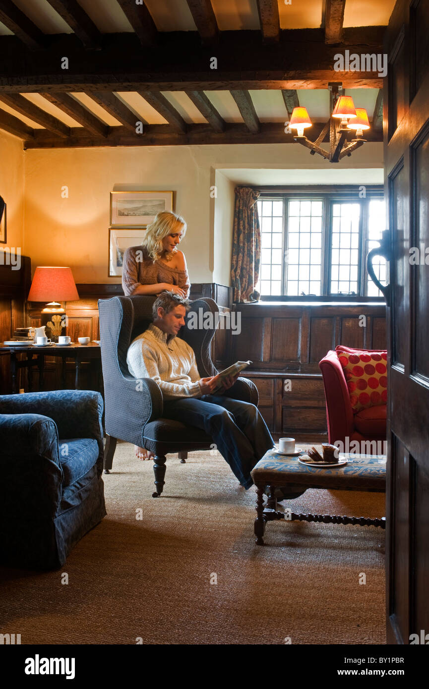 Gilar Farm, Snowdonia, North Wales.  A couple relax in the Sitting Room in this traditional Welsh farmhouse built - Stock Image