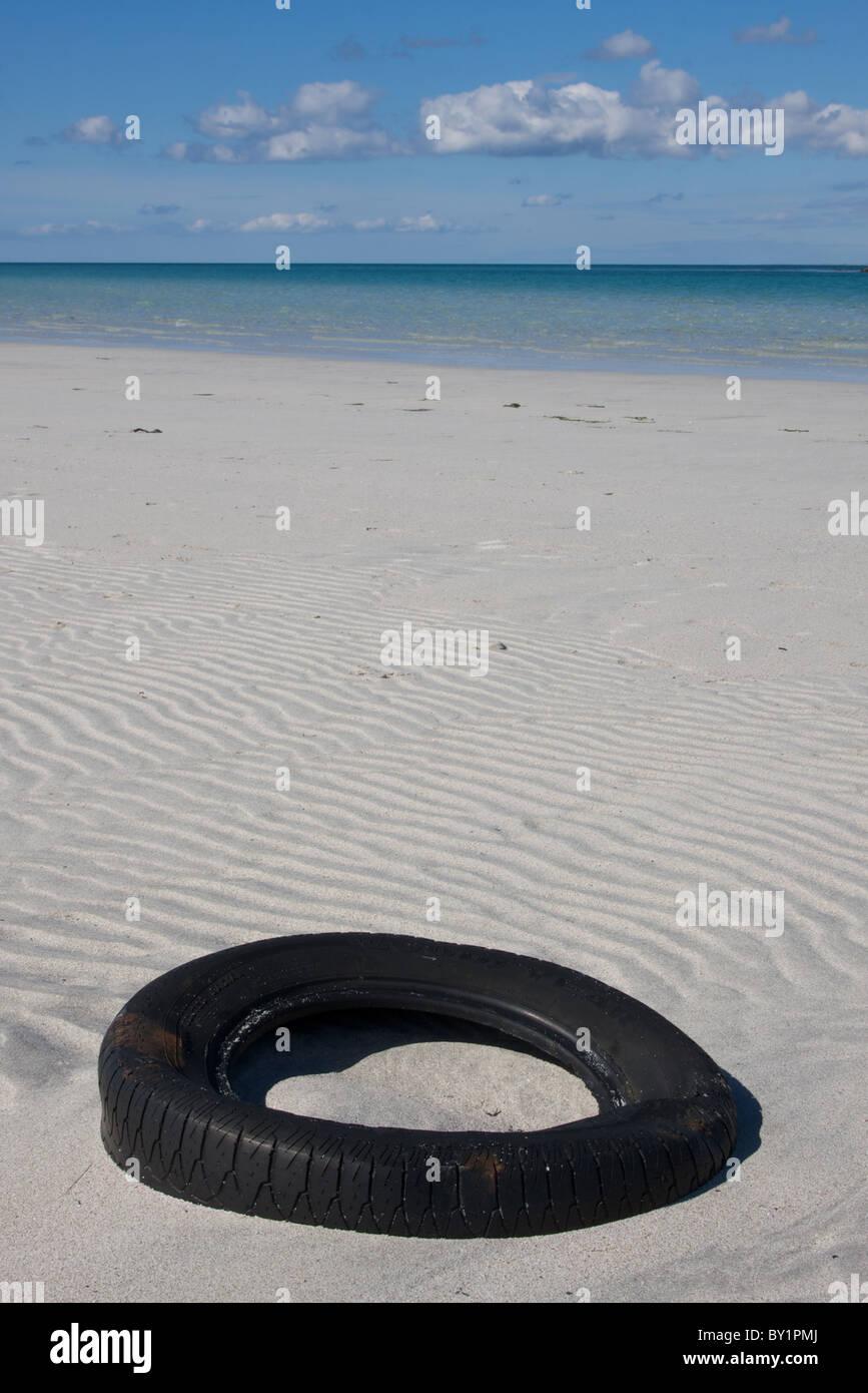 Discarded car tyre on Traigh Sgùrabhal beach, Eolaigearraidh, Barra, Outer Hebrides, Scotland, UK - Stock Image