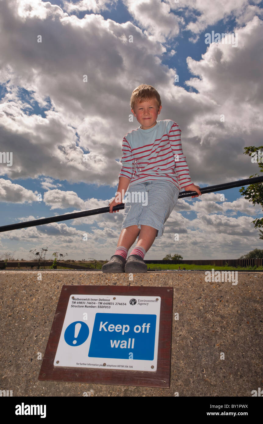 A MODEL RELEASED cheeky boy breaks the rules at Walberswick , Suffolk , England , Great Britain , Uk - Stock Image