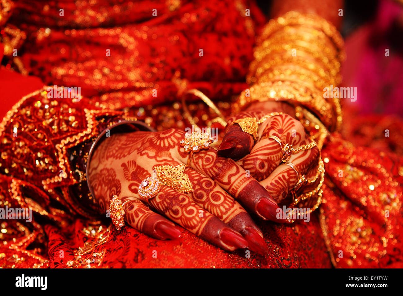 Indian bridal hand with henned hand n gold rings - Stock Image