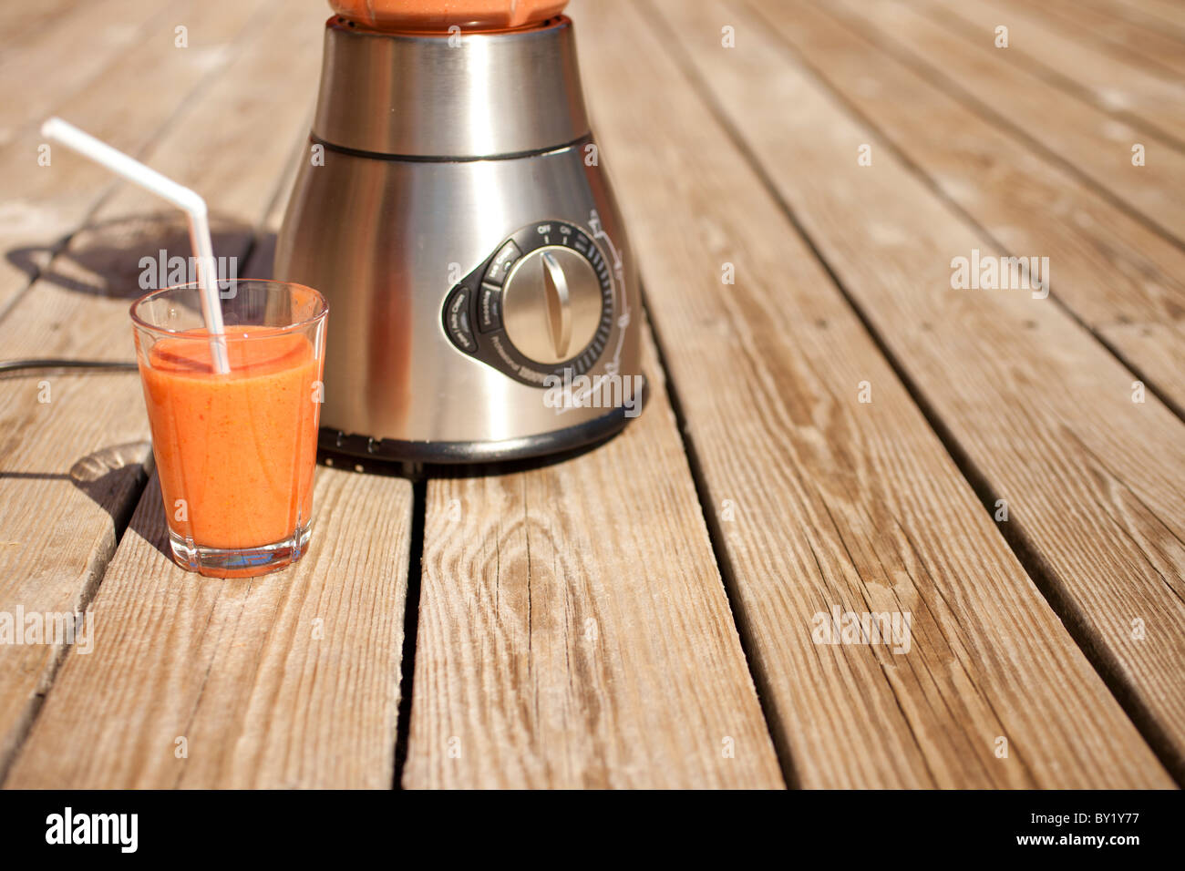 A glass of fruit smoothie with blender in background - Stock Image