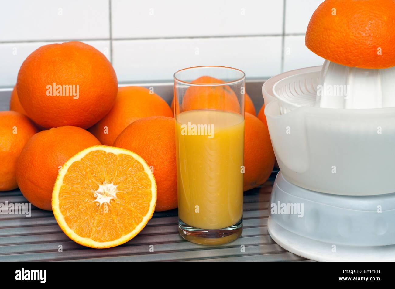 Preparing orange juice with a juice maker - Stock Image