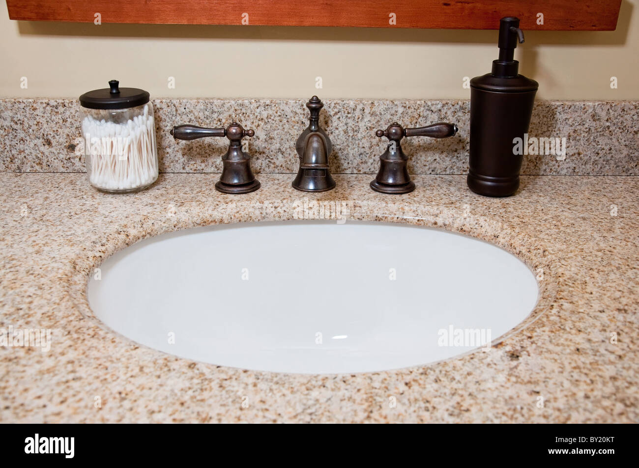 Bathroom sink and faucet with cotton swabs and soap dispenser. - Stock Image