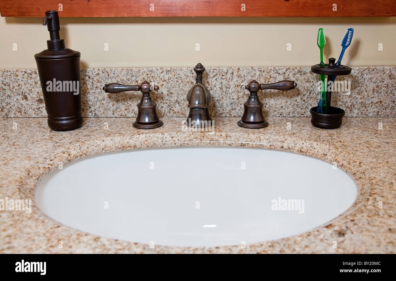 Bathroom sink and faucet with toothbrushes and soap dispenser Stock ...