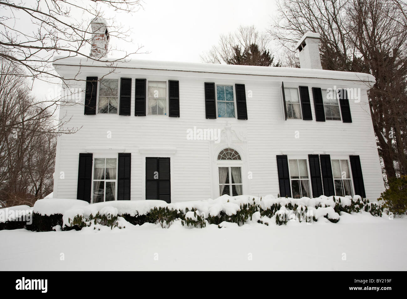 Snow is up to the window sills of a colonial home in Stockbridge, Massachusetts after a major snowstorm. - Stock Image