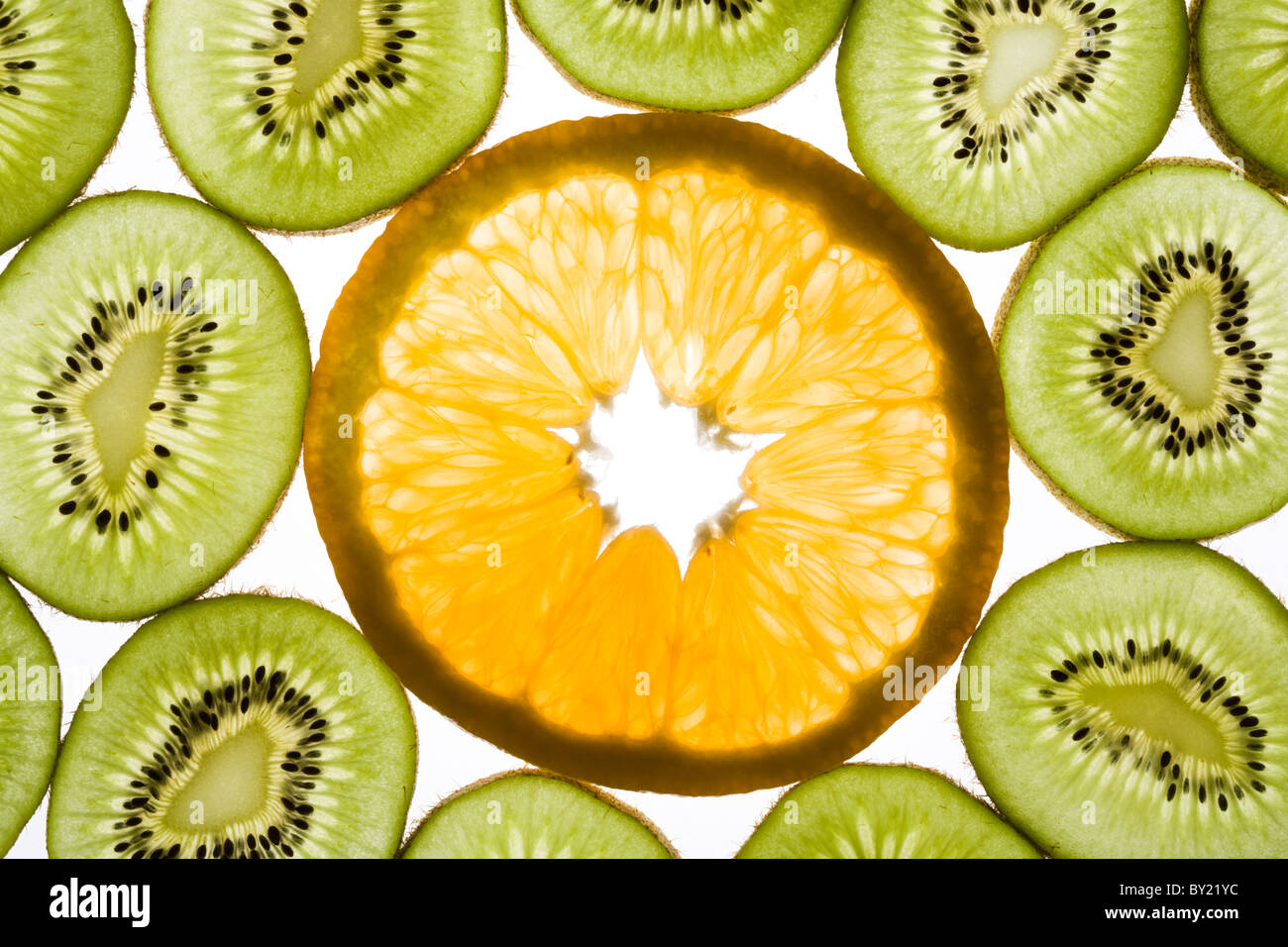Photo of orange in the middle of slices of kiwi - Stock Image