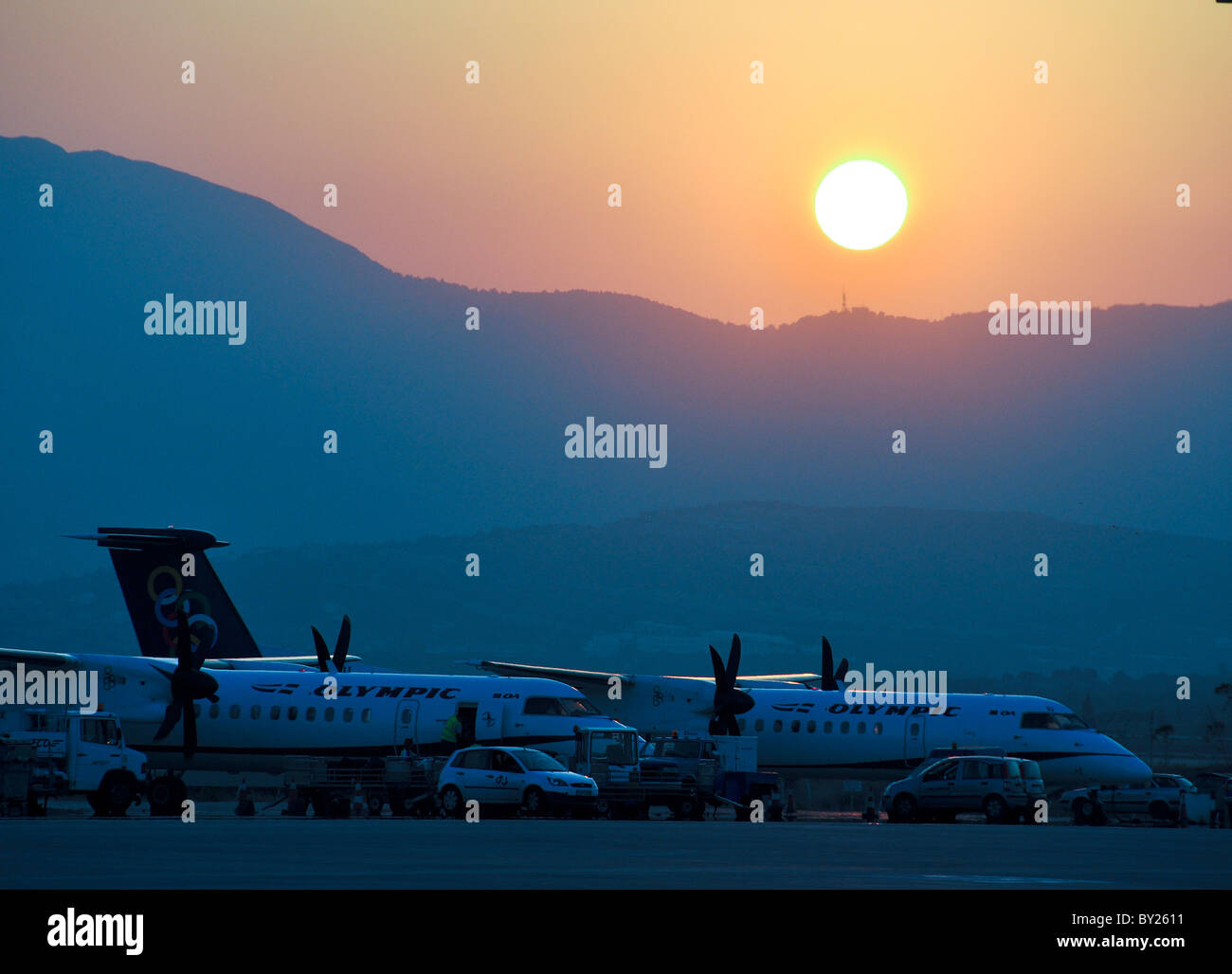 Greece, Athens Airport, Olympic Airlines Dash8 passanger planes on the ground at sunset - Stock Image