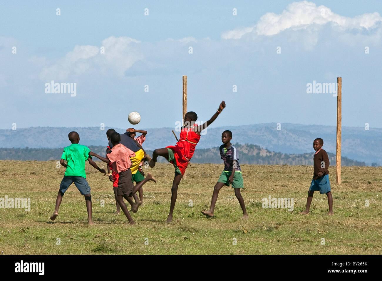Maasai schoolboys playing football on a makeshift pitch. Narok District, Kenya - Stock Image