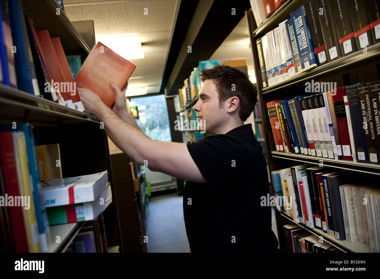 A mature student at Aberystwyth University taking a textbook from the shelf of the Law library, UK - Stock Image