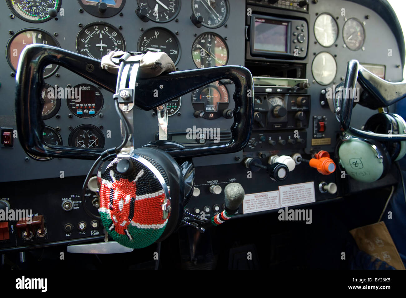 Kenya;  The controls of a Cessna light aircraft.  The pilot's headset is covered in a beaded Kenyan flag. Stock Photo