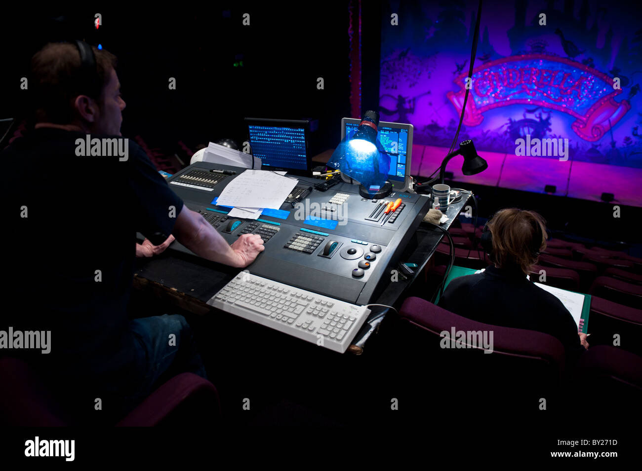 a man operating a digital lighting desk board in a theatre, designing the lights for a stage production, UK - Stock Image