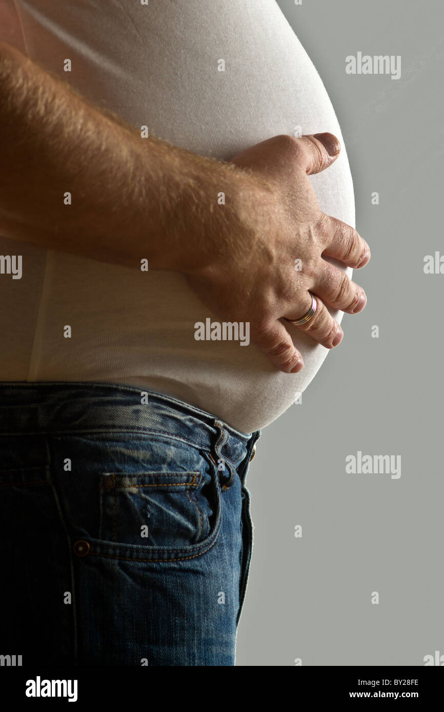 Overweight mid-adult man with hand on belly, mid section - Stock Image
