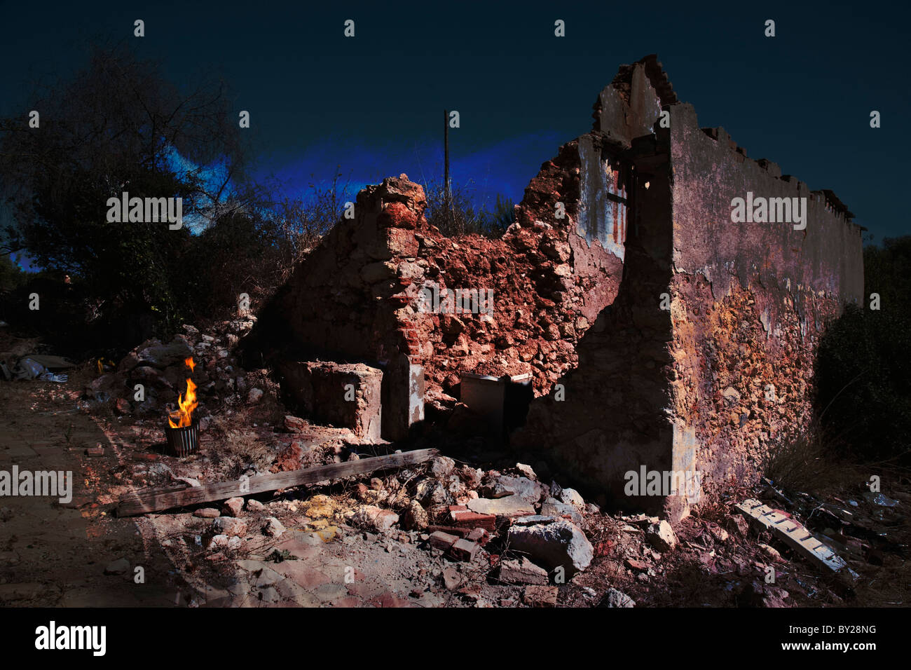 Creepy derelict decaying building at night with a fire burning in a metal basket. - Stock Image