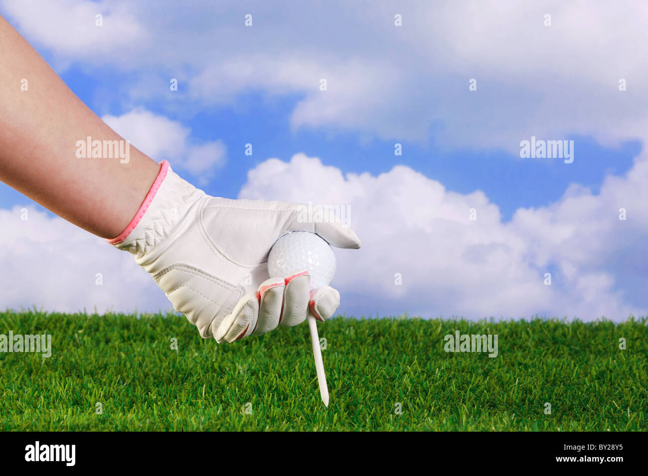 Photo of a ladies hand in white and pink glove placing a golf ball and tee into grass. - Stock Image