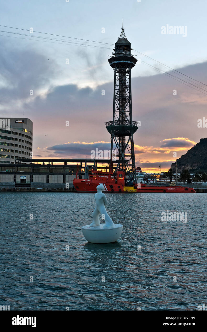 Cable car tower and man shape floating sculpture - buoy, Port Vell, harbour, Ciutat Vella, Barcelona, Spain - Stock Image