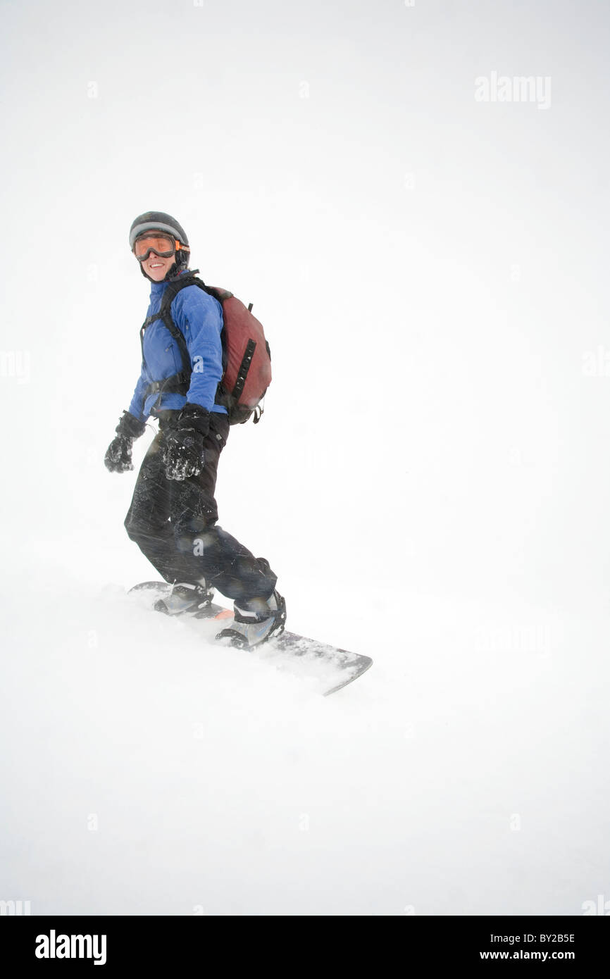 Young woman snowboarder poses for camera during stormy weather on Mount Hood, Oregon. - Stock Image