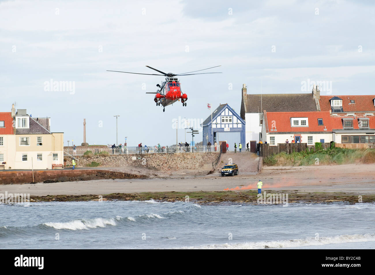 Search and rescue helicopter landing on a beach in North Berwick, Scotland. The site is marked by flares set by - Stock Image