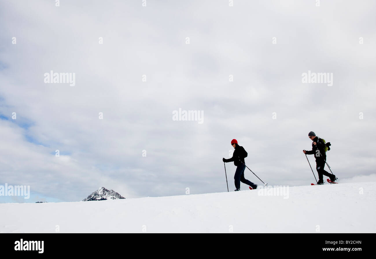 Two people snow shoeing along a ridge on an overcast day. Stock Photo