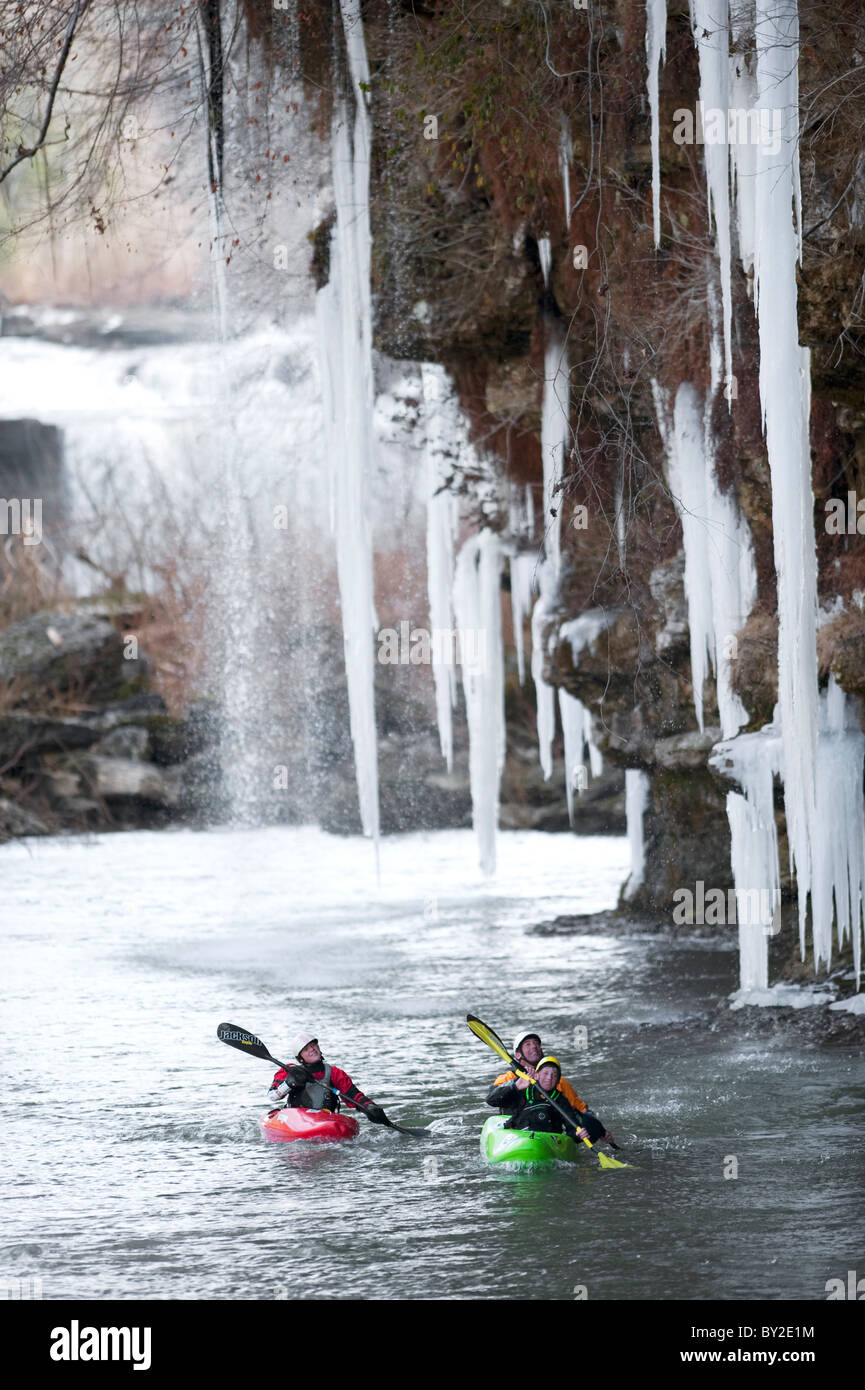 Three professional kayakers paddle under large icicles in Tennessee. - Stock Image