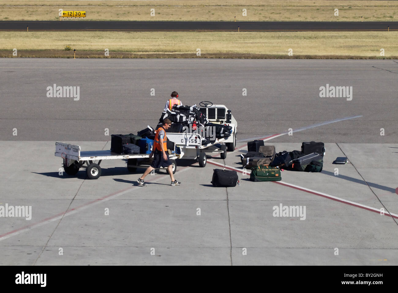 Mis handled baggage on the apron at Bozeman after falling of a heavily and over laden baggage trolley - Stock Image
