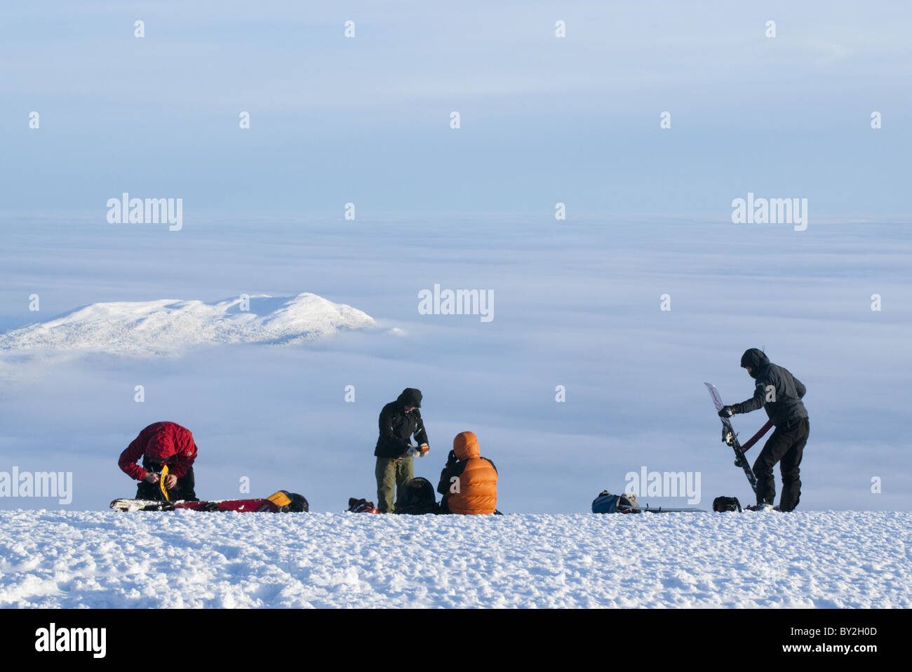 3 free skiers and a snowboarders getting ready for a ski-trip above the clouds in Kittelfjall, Sweden - Stock Image